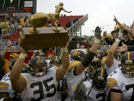 "With the black-and-gold faithful chanting ""Hawkeye State! Hawkeye State!"" Iowa's Erik Jensen hoists the Cy-Hawk Trophy after the Hawkeyes beat Iowa State, 40-21, Sept. 13, 2003, in Ames."