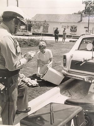 A police officer prepares to write a ticket in a 1969 photograph demonstrating a litter crackdown.