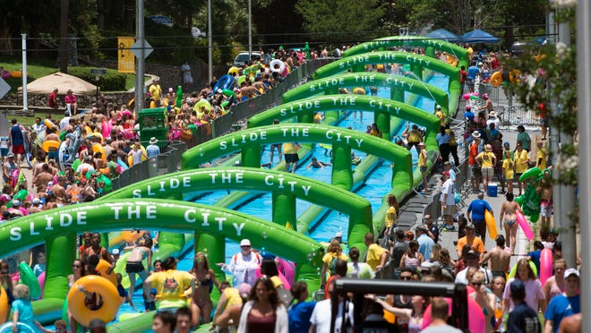 People stand in line and slide down Palafox St. Saturday afternoon during the Slide the City, a 1,000 foot water slide that traveled from about Jackson St. to north of Gregory St. in downtown Pensacola. Proceeds will benefit Gulf Coast Kids House.