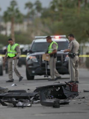 The mangled remnants of a golf cart are strewn across Desert Moon Drive Wednesday. Two men and two dogs in the cart were killed after the cart was struck by an SUV, authorities said.