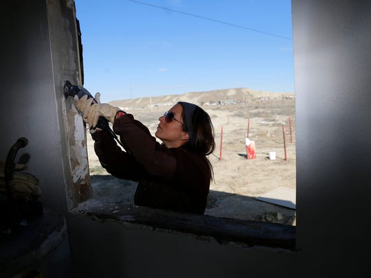 Tori Johnson works on a window frame Friday at the Hale residence in Hogback.