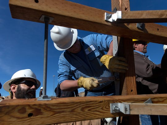At center, Farmington Electric Utility System Environmental Scientist Aaron Daley and helper, Jared Merryman, work on constructing an osprey platform on Thursday at Navajo Dam.
