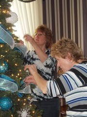 """Donna Ney and Mindy Peters decorate their tree at Vilas Rahr Mansion at Rahr-West Art Museum in Manitowoc. The tree will be part of """"Christmas in the Mansion"""" festivities."""