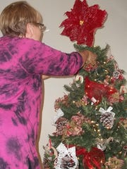 """Carol Entringer puts the finishing touches on her Christmas tree decorations, which will appear as part of """"Christmas in the Mansion"""" at Vilas Rahr Mansion at Rahr-West Art Museum in Manitowoc."""