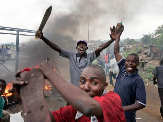 FILE - In this Monday, Jan. 28, 2008 file photo, Kenyan men from the Luo tribe armed with machetes and rocks enforce a makeshift roadblock, searching passing vehicles for Kikuyus trying to flee the town in order to kill them, during post-election violence on the main road to the Ugandan border near the airport in Kisumu, Kenya.