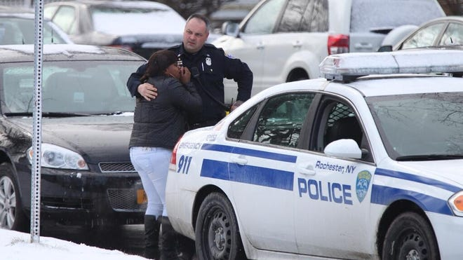 Police comfort a woman near 809 Chili Ave. the day the bodies were found.