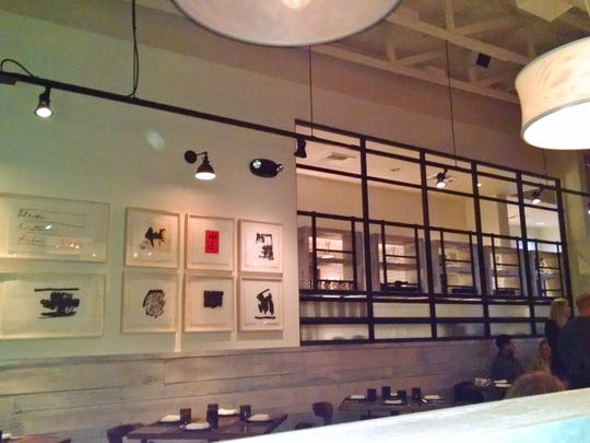 The interior includes washed wood, metal grids and artwork, all of which contribute to the restaurant's casual vibe.