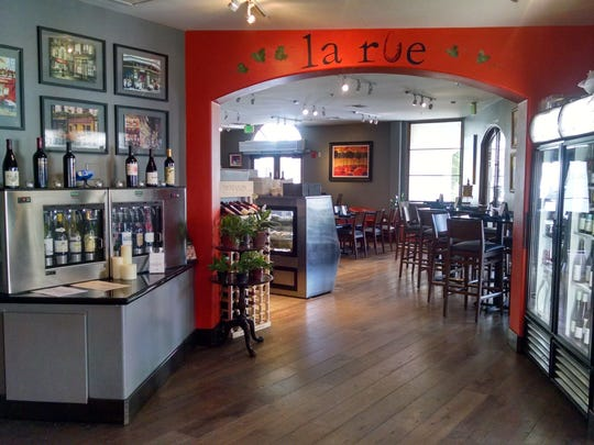 A warm pumpkin accent wall creates an inviting main dining at La Rue Cafe and Wine Bar.