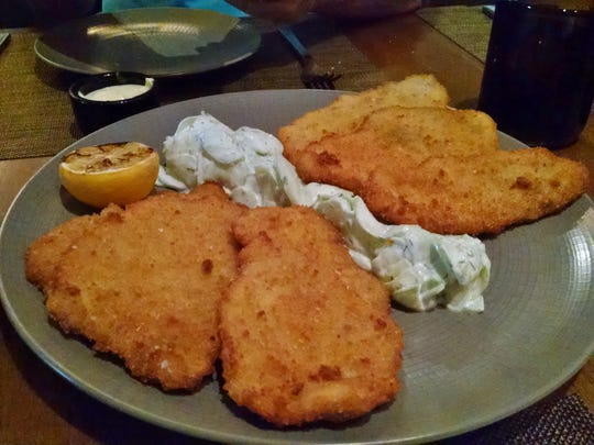Pork schnitzel with dill and sour cream cucumbers.