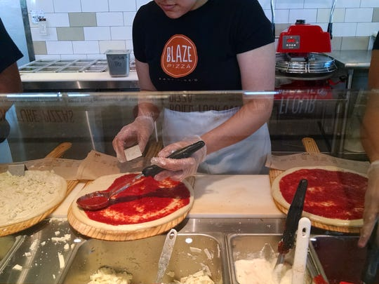 Tomato sauce is ladled onto the dough.