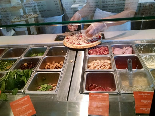 Customers can choose from a variety of toppings available at Blaze Pizza.