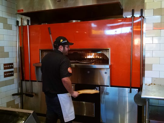A Blaze Pizza employee places a pizza in the oven for a quick firing.