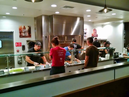 Pieology customers build a pizza to their liking assembly-line style.
