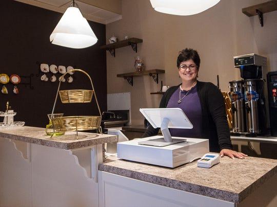 TeaScapes owner Kathleen Edinger stands over her new