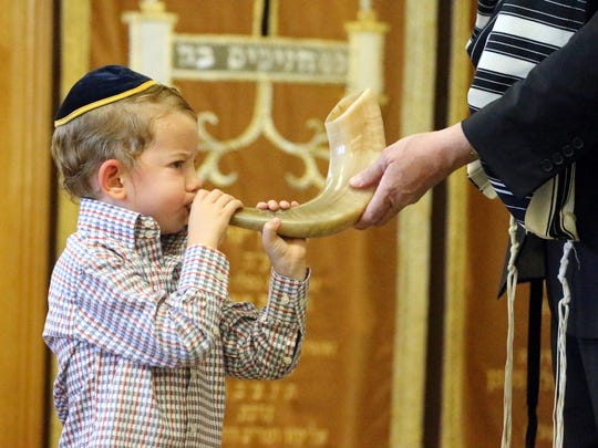 Menachem Greenberg, 3, tries blowing a shofar with help from his grandfather, Rabbi Yisrael Greenberg.