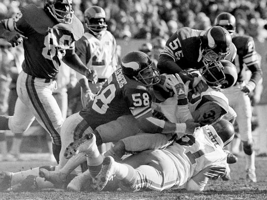 Los Angeles Rams L. McCutcheon (30) is stopped by Minnesota Vikings Wally Hilgenberg (58) and Amos Martin (55) in the NFC championship game at Bloomington, Dec. 26, 1976. Hilgenberg's wife is speaking out about consequences of concussions in football.