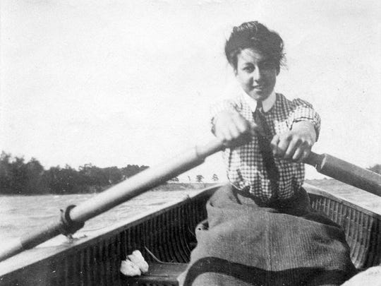 Old standby: A woman rows off Button Island in Lake