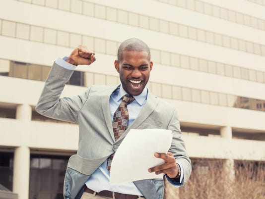 Successful young professional man celebrates success holding new contract documents