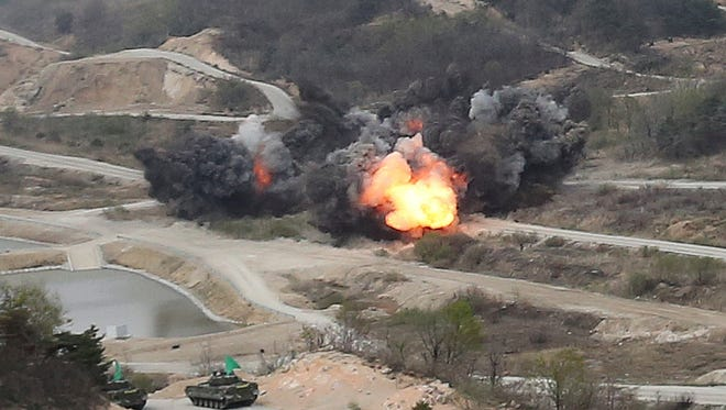 Flames rise as South Korean army's armored vehicles wait during South Korea-U.S. joint military live-fire drills at Seungjin Fire Training Field in Pocheon, South Korea, near the border with North Korea, on April 26, 2017.