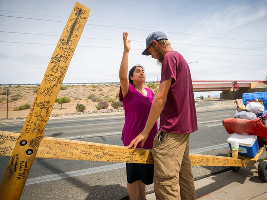 Juana Shaffer blesses Mitchell Manning on the side of the road near U.S. Route 70 in Las Cruces, NM, during his walking trip from Florida to California, Tuesday, August 9, 2016. Shaffer spotted Manning, who is engaged on a multi-month journey, walking from Florida to California while carrying a 12-foot wooden cross made of Western red-cedar, and pulled over to the side of the road to bless him and give him 80 dollars to help with his trek.