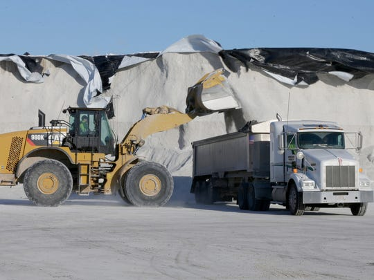 Salt is loaded up from a salt pile near the corner