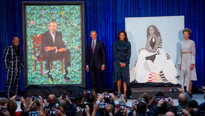 Former US President Barack Obama and First Lady Michelle Obama stand before their portraits and respective artists, Kehinde Wiley (L) and Amy Sherald (R), after an unveiling at the Smithsonian's National Portrait Gallery in Washington, DC, February 12, 2018.