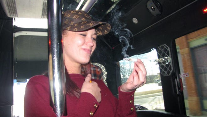 The legalization of recreational marijuana in Colorado has given rise to new enterprises, including a dozen or so that offer cannabis-themed tours. Here, Megan Page, a guide with My 420 Tours, takes a toke during a recent outing on a party bus. Credit: Jayne Clark/USA Today.