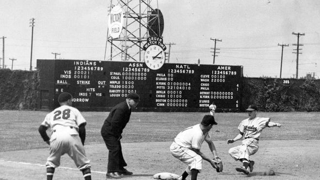 Milwaukee third baseman Billy Klaus slides in safely at third during a sixth-inning rally in the 1951 opener against the Indianapolis Indians at Victory Field. The Tribe's Nanny Fernandez takes the throw from center while Brewers manager Charlie Grimm and umpire Bill Jackowski watch.