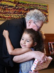 Margaret Warn-Walker gets a hug after getting a gift from Madelyn Lance, 3, at Walker's retirement reception June 9 at Metropolitan Exodus Community Church, which Warn-Walker has pastored.