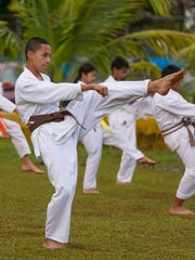 Edmund Borja, center, practices karate kicks during a  training session led by instructor Errol Lee at Matapang Beach Park in Tumon on April 11.