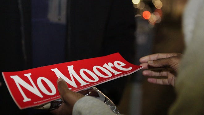 "Tori Sisson, right, receives a gift of chocolate and a ""No Moore"" sticker, named after Roy Moore, from a supporter, near the Montgomery County Courthouse on Sunday, Feb. 8, 2015. Alabama Chief Justice Roy Moore sent a letter to probate judges Sunday evening ordering them to refuse to issue same-sex marriage licenses."