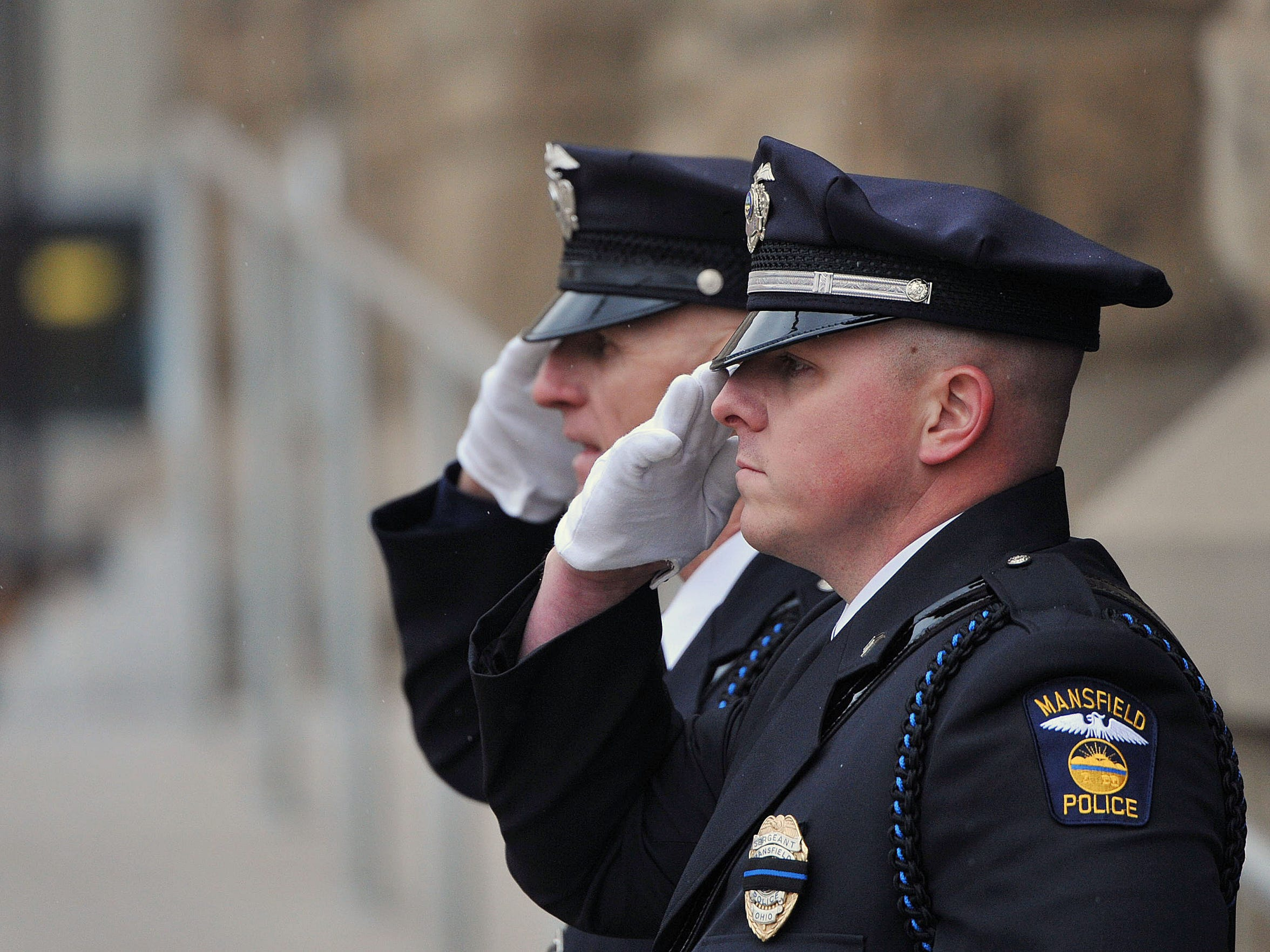 Mansfield police officers salute as the casket of John