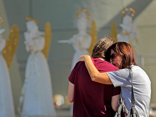 People comfort each other at a public memorial for