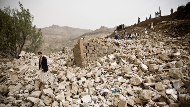Yemenis search for survivors in the rubble of houses destroyed by Saudi-led airstrikes in a village near Sanaa, Yemen.