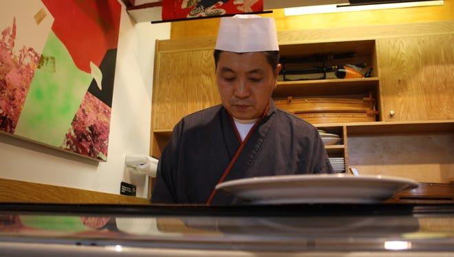 Sakura Japanese Restaurant owner Danny Kim, 56, of Endicott, prepares a Volcano Roll at the restaurant's sushi bar.