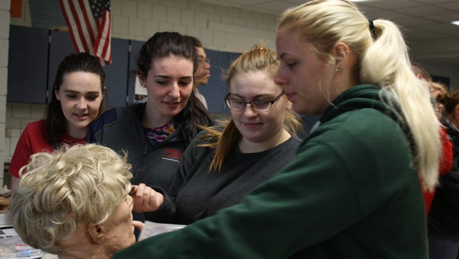 From left: Grace Mallon, 16, Kiley Buck, 17, Amber Wade, 18, and Makayla Hoyt, 18, all of Binghamton, view a demonstration head brought to their class by David Tinklepaugh.