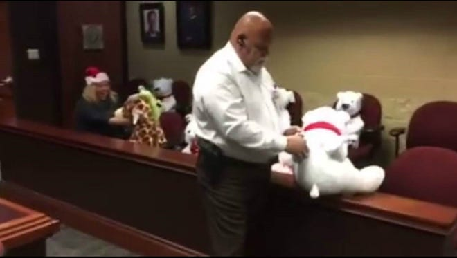 Bailiff Roger Flores, who works with County Court-at-Law Judge Timothy McCoy, cuffs a stuffed bear during the court staff's holiday-themed mannequin challenge.