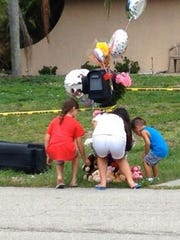 Hayley Latimore, 9, Chloe Latimore, 11, and Adrian Smith, 3, put flowers on a memorial for slain San Carlos Park family