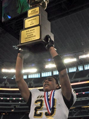 Crowell running back Daniel Clark (23) hoists the trophy in the air after the Wildcats' 78-52 over May during the 2014 UIL Six-Man Division I state championship football game at AT&T Stadium in Arlington.