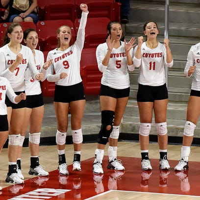 USD volleyball players cheer on their teammates while