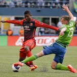 Seattle Sounders' Dylan Remick, right, tackles Portland Timbers' Dairon Asprilla, left, in the first half of an MLS soccer match, Sunday, April 26, 2015, in Seattle.