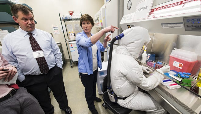 Darren Berger and Kelly Moore describe to a group of media representatives the personal protective equipment (PPE) worn by a researcher to demonstrate proper biosafety practice during a tour of the Influenza Research Institute (IRI) at the University of Wisconsin-Madison on Feb. 2, 2014. Berger is assistant director and facilities engineer in the Office of Biological Safety and Moore is the IRI facility manager. The high-security research facility was closed down for annual decontamination, cleaning and maintenance.
