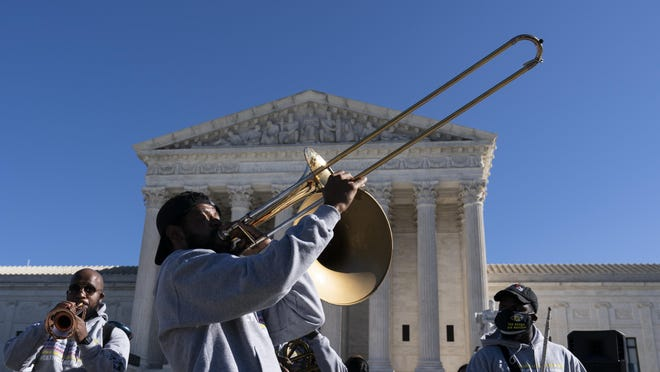 "The ""Too Much Talent,"" band performs in front of the U.S. Supreme Court as arguments are heard about the Affordable Care Act, Tuesday, Nov. 10, 2020, in Washington."