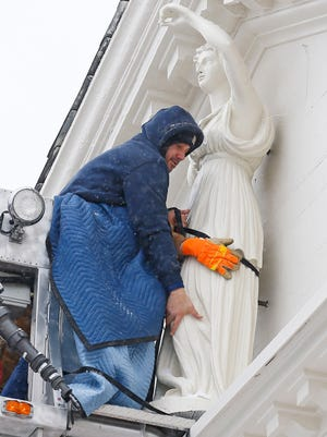 Alex Matos of Kunzman Construction attempts to move the Lady Justice statue onto her bolts. After two attempts on two different vehicles the installation of Morristown's Lady Justice was canceled. When the first attempt came up unexpectedly short because of the reach of the crane boom, the Morris Township Fire Department brought out its ladder truck, reaching the ledge but the crew had problems aligning the bolts that attach Justice to the courthouse with holes drilled in the tympanum, the ornamental ledge on which Justice stands just below the roof of the Morristown courthouse. December 30, 2017.