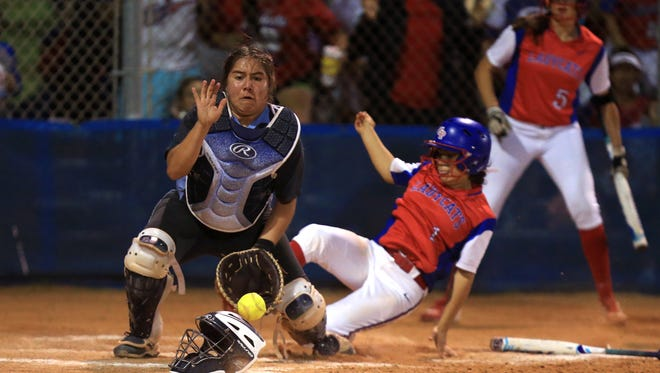 Gregory-Portland's Harley Escamilla ties the game as she scores on a throwing error as Carroll pitcher Olga Zamarripa gets the ball late field the ball at the Gregory-Portland High School softball field on March 24, 2017.