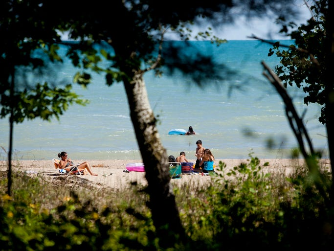 People enjoy the sun and water August 28, 2014 at Lakeport State Park in Burtchville Township.