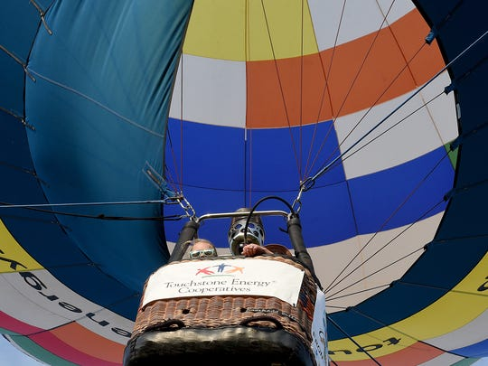 Kynlee Adolph, 9, peers over the edge of a hot air balloon during a tethered balloon ride on the opening day of the 2018 Coshocton Hot Air Balloon Festival on Thursday, June 7, 2018 at the Coshocton County Fairgrounds.