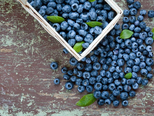 Wooden basket full of fresh blueberries on table
