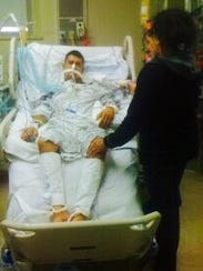 Adam Gonzales lies in a hospital bed with tubes connected