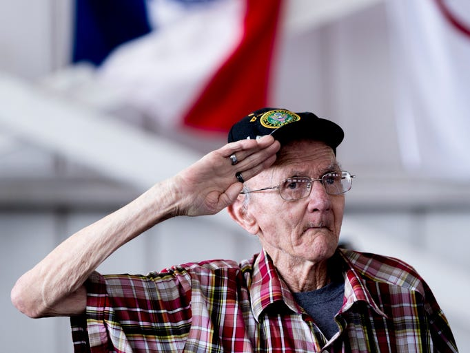 WWII veteran Donald Collett salutes during the national
